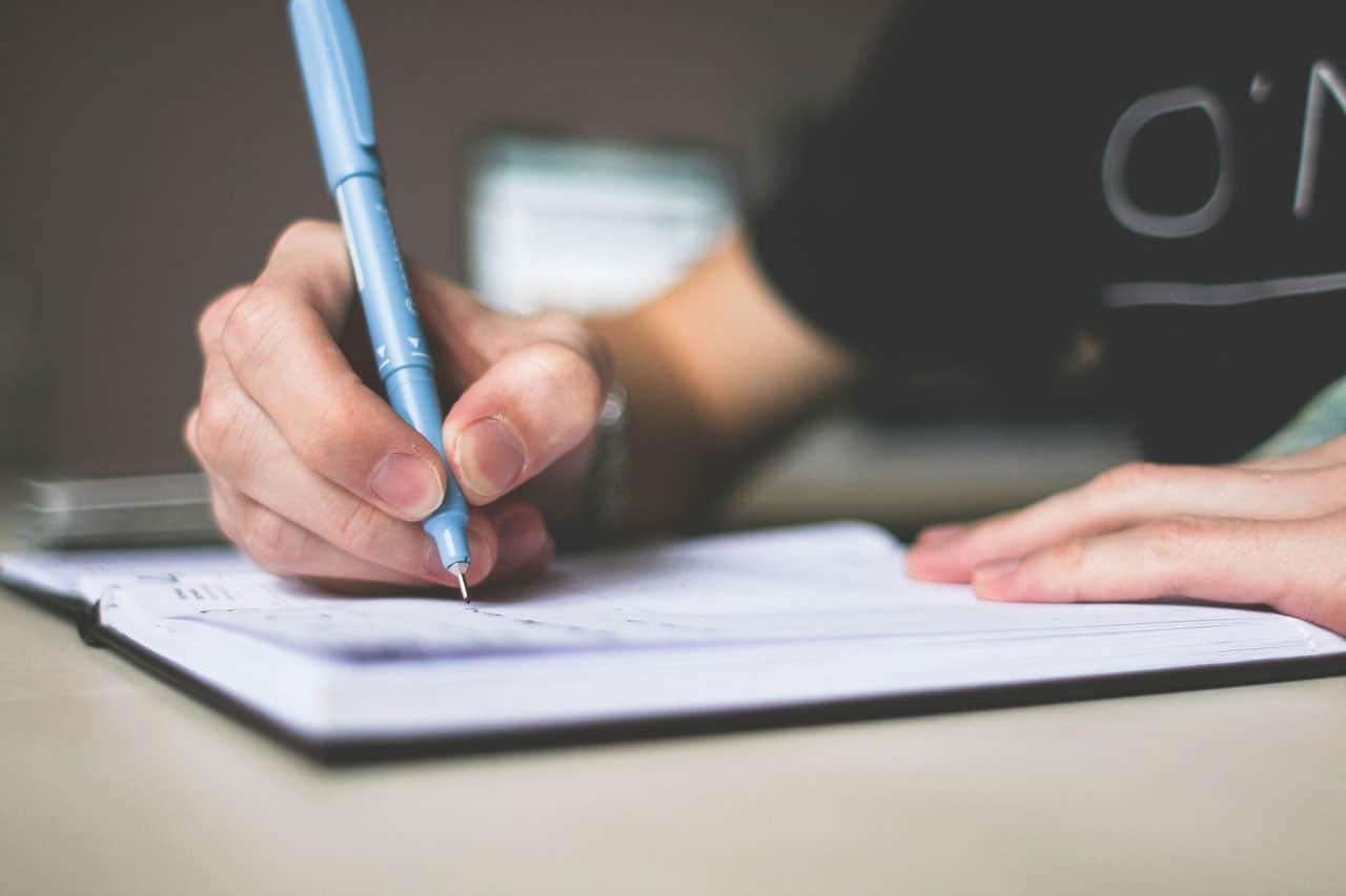 אדם כותב בעט בתוך יומן