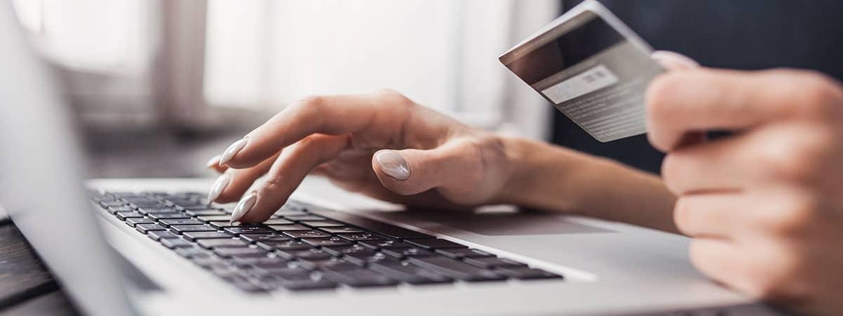 יד מחזיקה כרטיס אשראי ומקלידה בלפטופ