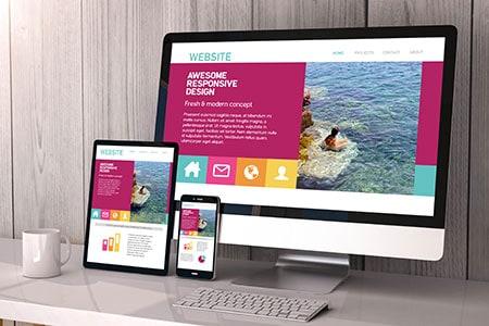 מסך מחשב, מסך פלאפון ומסך אייפד מונחים על שולחן