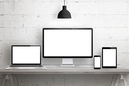 מסך מחשב, לפטופ פתוח, מסך אייפד ומסך פלאפון מונחים על שולחן כתיבה